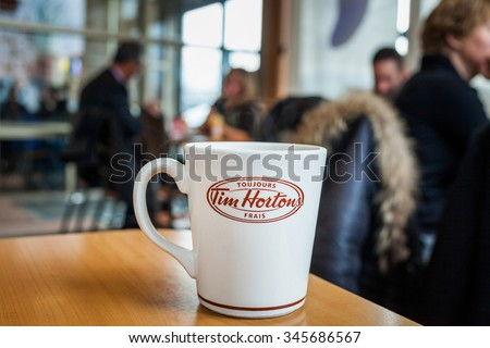 Montreal, CANADA - November 30th 2015:Fresh French Coffee Cup on a Table Inside a Time Hortons Restaurant in the Morning with Consumers in the Background - stock photo