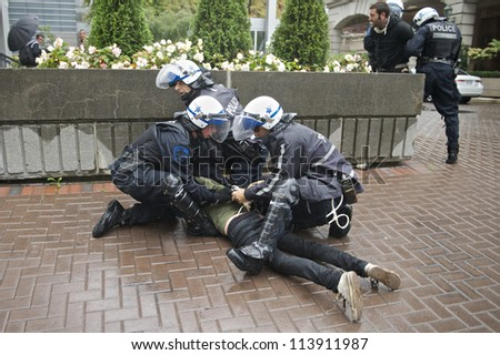 MONTREAL, CANADA - SEPTEMBER 22: Riot police arrest unidentified protesters who damaged a police vehicle while taking part in a march demanding free education on September 22, 2012 in Montreal. - stock photo