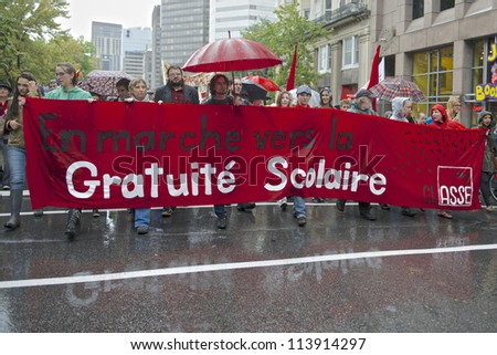 "MONTREAL, CANADA - SEPTEMBER 22: Students march behind a banner meaning ""marching towards free education"" during a demonstration demanding free education on September 22, 2012 in Montreal. - stock photo"