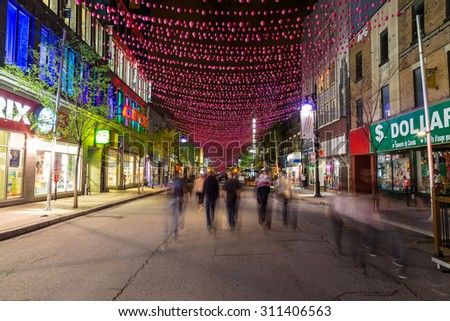 MONTREAL CANADA - 17TH MAY 2015: A view along Saint Catherine Street in Montreal at night showing businesses and the blur of people. - stock photo