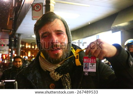MONTREAL - MARCH 27: A journalist holds up his press pass after being pepper sprayed by police during a student protest in Montreal on March 27, 2015. - stock photo