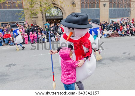 MONTREAL, QUEBEC, CANADA - NOVEMBER 21, 2015 : Little girl holding Snowman in the 65th edition of the Santa Claus Parade Destination Centre-ville (Defile du Pere Noel) along Saint Catherine Street. - stock photo