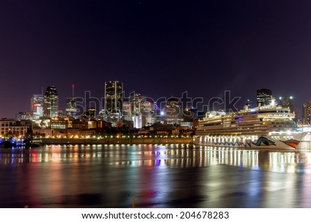 Montreal,Quebec,Canada- October 3 - 2013 : Port of Montreal with Aida cruise Boat in the port, and Downtown Montreal in background.  - stock photo