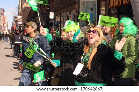 Montreal, Quebec, Canada - St. Patrick 's Day March 17, 2013 in Montreal, Quebec.  Spectators cheer on marchers along St. Catherine Street during  annual St. Patrick's Day parade. - stock photo