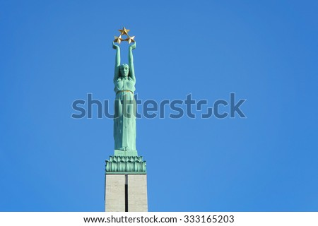 Monument of freedom in Riga. Woman holding three gold stars which symbolise three regions of Latvia. - stock photo