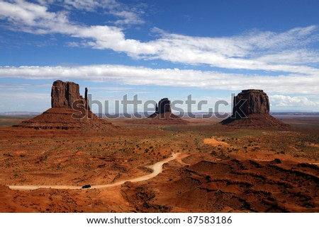 Monument Valley against a deep blue cloudy sky - stock photo