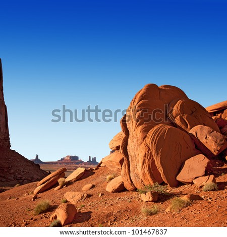 Monument Valley, Utah, USA, showing typical rock formations. The sandstone is a very red colour due to high iron content. Blue sky space for your text. - stock photo