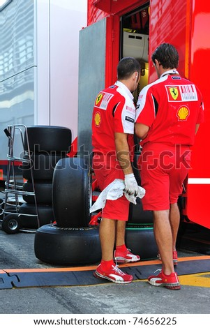 MONZA - SEPTEMBER 11: Mechanics from team Ferrari are cleaning up the tires, at the back of the pitbox of formula 1 on September 11, 2010 in Monza, Italy - stock photo