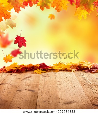 Moody autumn background with falling leaves on wooden planks - stock photo