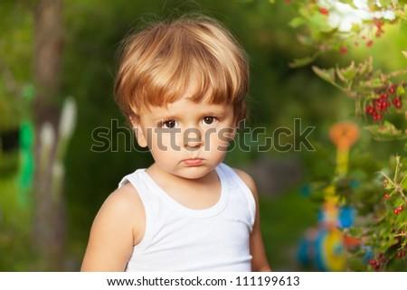 moody boy's portrait in the garden - stock photo