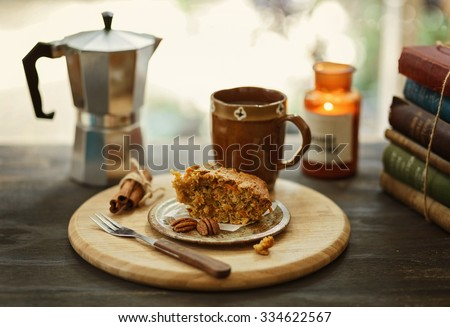 Moody Instagram looking image of morning coffee and a piece of carrot cake  on a rustic table. Color toning, filters, retro effect, shallow depth of field, selective focus - stock photo