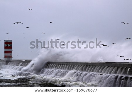 Moody seascape with big wave, pier, lighthouse and seagulls flying over crashing wave - stock photo