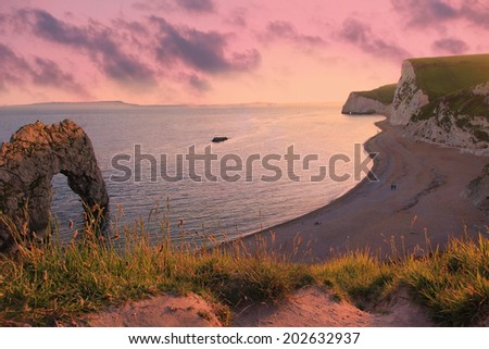 moody sunset scenery at durdle door beach, dorset - stock photo