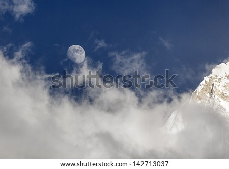 Moon and slope of the Nuptse (7864 m) in a mist (view from Kala Patthar) - Everest region, Nepal, Himalayas - stock photo