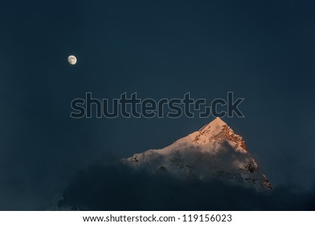 Moon and top of the Nuptse (7864 m) at sunset (view from Kala Patthar) - Everest region, Nepal - stock photo