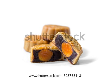 moon cakes in a Chinese mid-autumn festival on white cut in a half to see black sesame and egg yolk stuff - stock photo