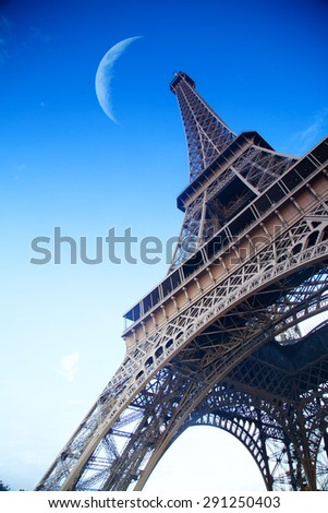 moon hanging in the sky directly over the Eiffel Tower. Paris, France - stock photo