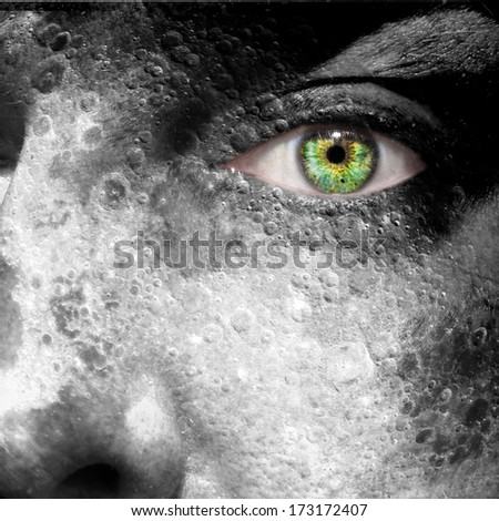Moon image superimposed on a man's face with green eye - elements of this image furnished by NASA - stock photo
