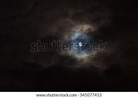 Moon on black cloudy dramatic sky background. - stock photo