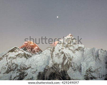 Moon over Mount Everest (8848 m) and Nuptse (7864 m) at sunset (view from Kala Patthar) - Everest region, Nepal, Himalatas - stock photo