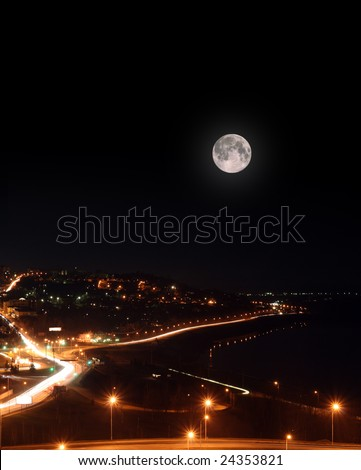 moon over night city with motion light roads and embankment - stock photo