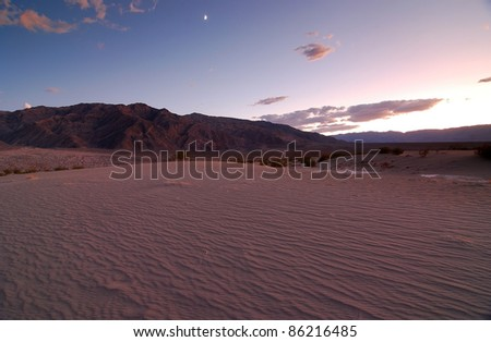 Moon passing over mountains with sunset casting soft glow on desert sand dunes in Death Valley National Park. - stock photo