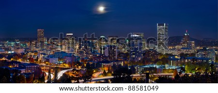 Moon Rise Over Portland Oregon City Skyline and Light Trails at Blue Hour - stock photo