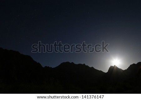 Moon rising over the silhouetted Tinajas Altas Mountains in Arizona, USA. Nice clean lines of the mountains along the horizon. Dark night gives impression of desolation in the Sonoran Desert. - stock photo