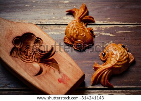 Mooncake cookies together with wooden mould on wooden background - stock photo