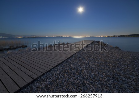 moonlight on the lake pier and rocks - stock photo
