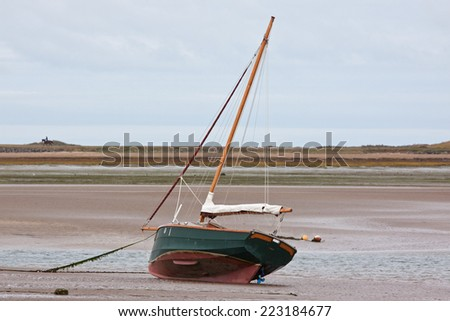 Moored sail boat at low tide sitting serenely on the bed of the Torridge estuary UK - stock photo