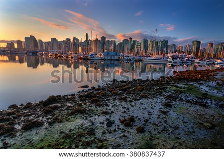 Moored yachts and boats and glass buildings, during sunset - stock photo
