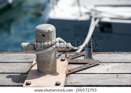 mooring bollard with a fixed rope on the pier - stock photo