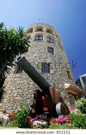 Moorish Tower and Cannon in Puerto Banus in the port of Puerto Banus in Spain - stock photo