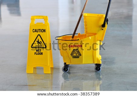 Mop bucket and caution sign on wet floor - stock photo