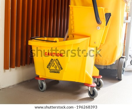 Mop bucket and wringer with caution sign on the floor in office building - stock photo