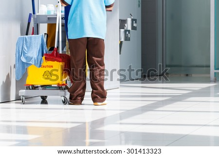 Mop bucket on cleaning in process and worker - stock photo