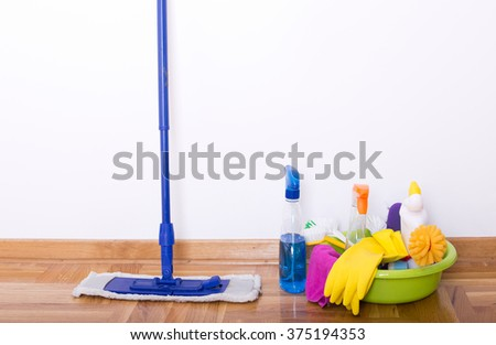 Mopping stick and washbasin full of cleaning supplies and equipment standing on parquet beside white wall - stock photo