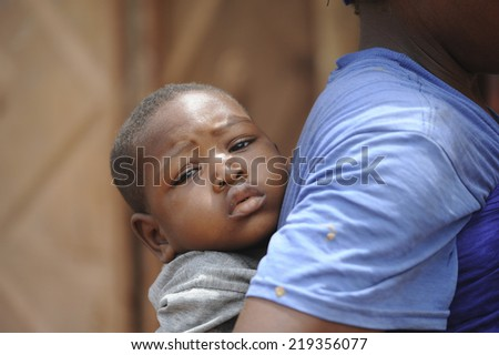 Mopti, Mali, Africa. August, 26, 2011. Mother carrying her child to the doctor in Mopti - stock photo