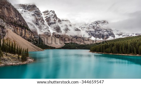 Moraine lake in the clouds - stock photo