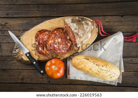 Morcon, a Spanish sausage like chorizo with bread and tomato on the cutting board - stock photo
