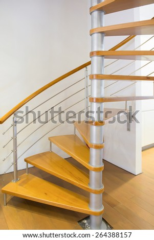 morden spiral stairs with wooden steps inside a house - stock photo