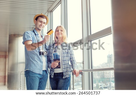 More opportunities for travel. Young dreaming couple holding credit card while standing in the airport terminal. - stock photo