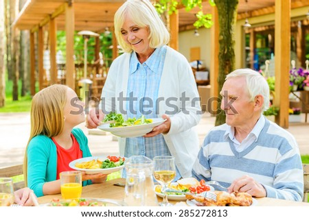More salad? Cheerful senior woman serving fresh salad while her husband and granddaughter sitting at the dining table outdoors  - stock photo