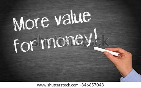 More value for money - female hand with chalk writing text on blackboard - stock photo