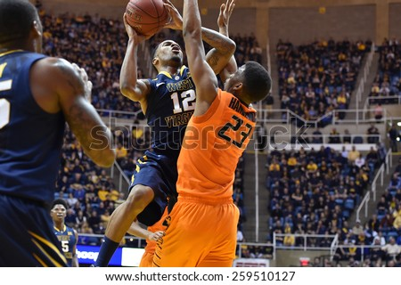MORGANTOWN, WV - MARCH 7: WVU guard Tarik Phillip (12) shoots over OSU guard/forward Leyton Hammonds (23) during the Big 12 Conference college basketball game March 7, 2015 in Morgantown, WV.  - stock photo