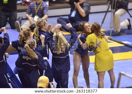 MORGANTOWN, WV - MARCH 8: WVU gymnast Brooklyn Doggette is congratulated by a coach and teammates following her balance beam routine during a dual meet March 8, 2015 in Morgantown, WV.  - stock photo