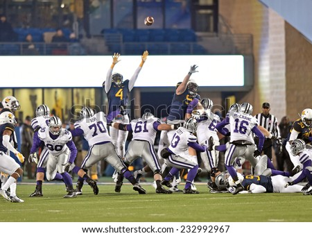 MORGANTOWN, WV - NOVEMBER 20: West Virginia Mountaineers defensive lineman Shaquille Riddick (4) leaps to try and block a kick during a football game November 20, 2014 in Morgantown, WV.  - stock photo