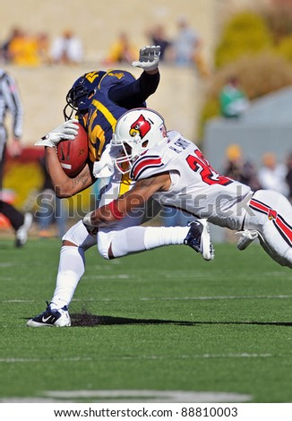 MORGANTOWN, WV - NOVEMBER 5: West Virginia receiver Willie Millhouse (#85) is tackled by a defender in the Big East football game against Louisville November 5, 2011 in Morgantown, WV - stock photo
