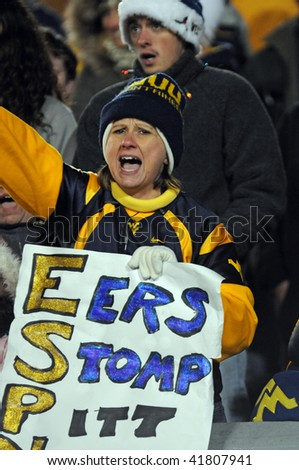 MORGANTOWN, WV - NOVEMBER 27: West Virginia University football fan cheers her team on with a homemade sign during WVU's upset 16-13 win over Pitt November 27, 2009 in Morgantown, WV. - stock photo